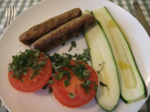 Baked sausages tomatoes and courgette